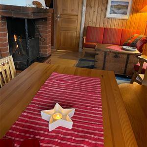 Röd duk på bordet och ett ljus format som en stjärna och en brasa vid soffan i bakgrunden.