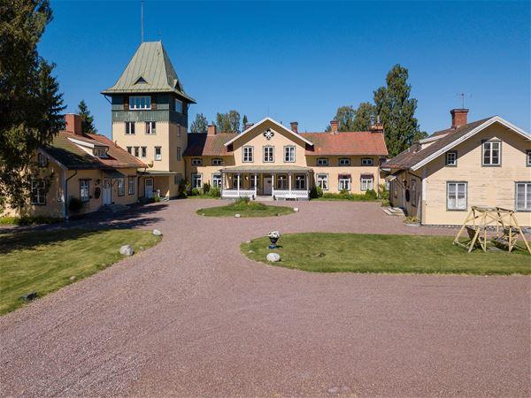 Exteriörbild med grusplan framför på Ulfshyttans Herrgård.