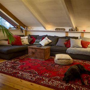 Soffa med kuddar på röd matta.
