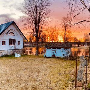 Utsikt över vitt hus vid sjö i solnedgången.