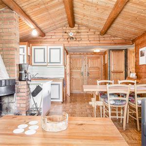 Interiörbild med öppen spis och bord och stolar.