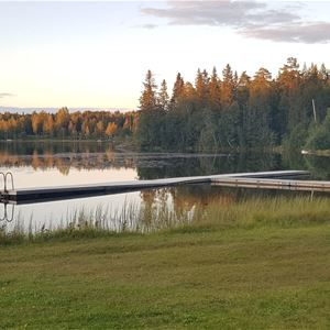 En brygga vid sjö i solnedgången.