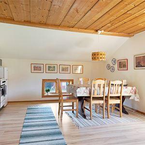 Köksavdelning och stort rum med matbord och stolar.