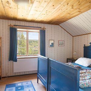 Sovrum med blå dubbelsäng och en våningssäng i furu, fönster med utsikt.