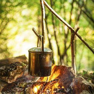 Koppargryta som hänger på en pinne över öppen eld.