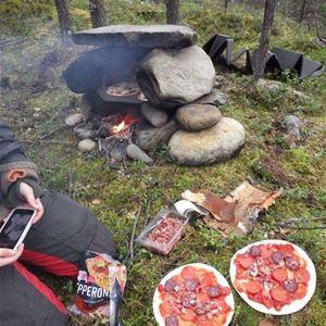 Två pizzor ligger på mossan och elden är tänd mellan några stora stenar.