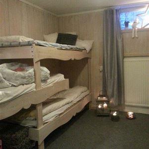 Sovrum i källarplan med våningssäng, fönster och ljuslyktor.