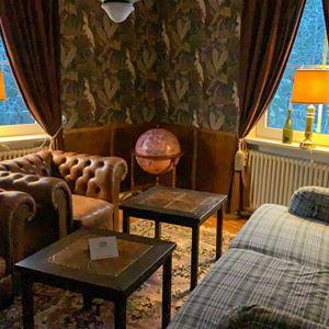 Vardagsrum med beige soffa och två bruna skinnfåtöljer.