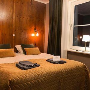 Dubbelsäng med guldfärgat överkast, lampor som lyser på väggen.