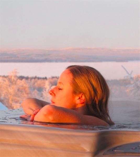 En kvinna njuter i en bubbelpool med Siljan och frostklädda träd i bakgrunden.
