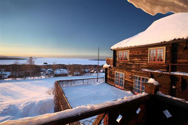 Brunt timmerhus med röda fönster och snö på taket.