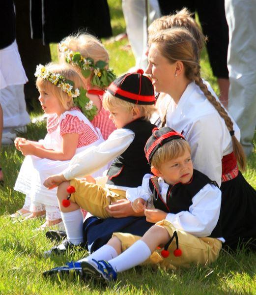 Barn i folkdräkt och med blomsterkransar i håret sitter på en gräsmatta.