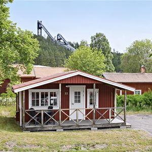 Rödmålad campingstuga med hopptornen i bakgrunden.