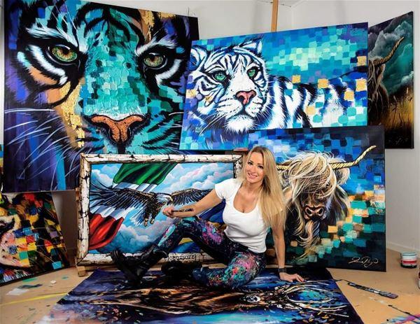 © Copy: https://www.facebook.com/events/449519626079435/, Kvinna med lång ljus hår sitter på golvet framför tavlor med tigrar.