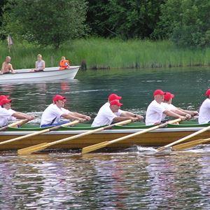 Många män ror i kyrkbåt.