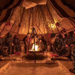 © Malangen Resort, Gjester sitter rundt bålet inne i lavvo