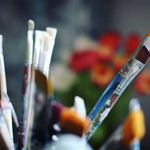 Flera penslar med en suddig blombukett i bakgrunden.