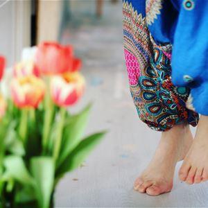 En persons fötter som står framför en blombukett.