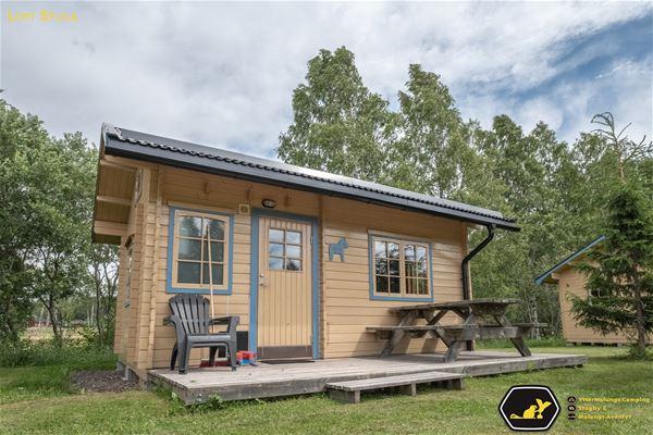 Liten, gul stuga med blåa fönsterfoder och ett picknickbord på altanen.