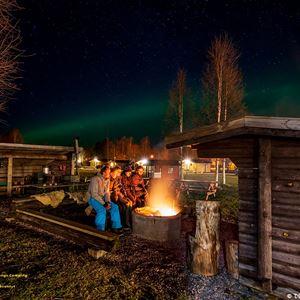 Några personer sitter vid en lägereld i mörkret, framför en slogbod.