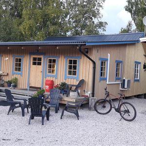 Gulmålat hus med utemöbler framför huset, på en grusplan.
