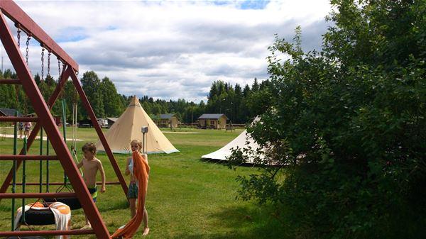 Två barn vid en gungställning och två naturfärgade tält i bakgrunden.
