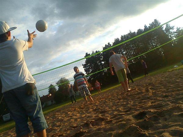 Några personer spelar volleyboll på sanden.