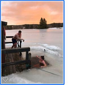 En kvinna badar i en isvak i solnedgången och en man står på en brygga och tittar på.