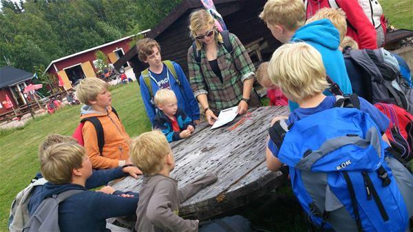 Några barn som står samlade runt ett bord av trä och lyssnar på en ledare.