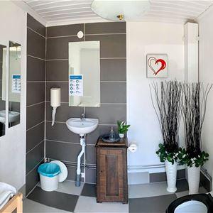 Toalett med handfat och skötbord.