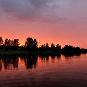 Solnedgång vid sjö och skog.