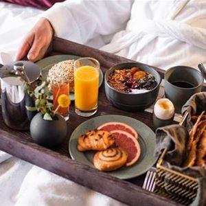 En stor frukostbricka med ett glas juice, kaffe, fralla och ägg.