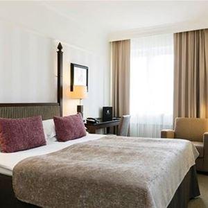 En dubbelsäng i ett av hotellrummen med ett skrivbord och stol bredvid sängen.