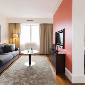 Soffa med soffbord och tv på väggen.