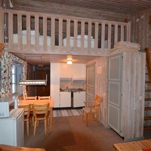 Lägenhet med kylskåp, micro, matplats och ett loft med sängar.
