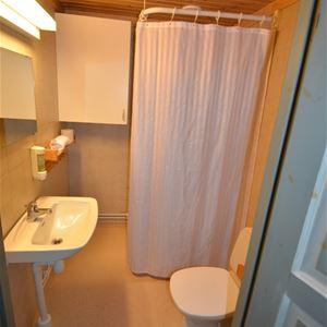 Badrum med gula väggar och golv, dusch, toalett och handfat.