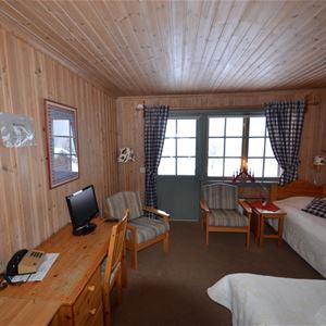 Två enkelsängar placerade i vinkel och ett skrivbord i ett rum med furupanel på väggarna.