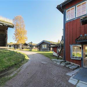 Rött hus med blåa knutar och en grusväg som leder till flera gråa timmerstugor.