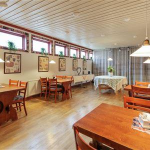 Restaurang med flera furubord med stolar.
