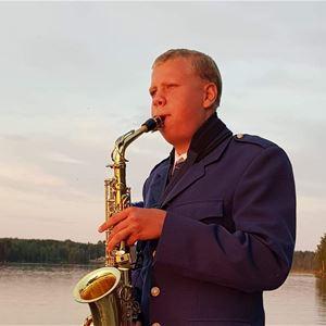Johan Stefansson,  © Johan Stefansson, En man som blåser i sin saxofon och har sjön bakom sig.