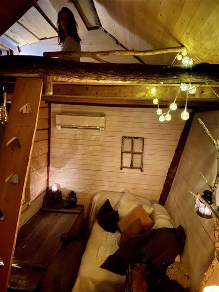 Interiör i Tiny House med timmerväggar, soffa,  ljusslingor mm.
