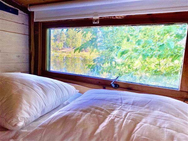 Säng intill fönster och sjöutsikt.
