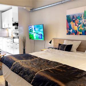 Sovrum och kök i bakgrunden