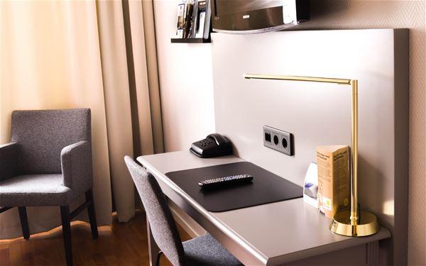 Skrivbord och en fåtölj på rummet.