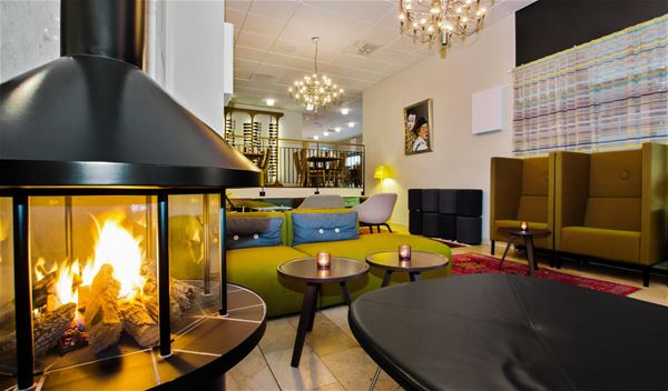 Lounge med fåtöljer intill en kamin.