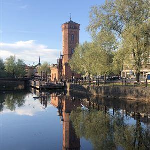 © Faluguide.se, Faluån med spegelblankt vatten, grönskande träd och hög smal byggnad i tegel i bakgrunden.