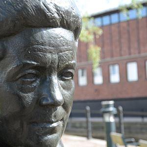 © falun.se, Staty av Selma Lagerlöf, röd tegelbyggnad i bakgrunden.