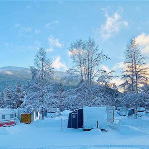 Husvagnar i vinterskrud med fjäll i bakgrunden.