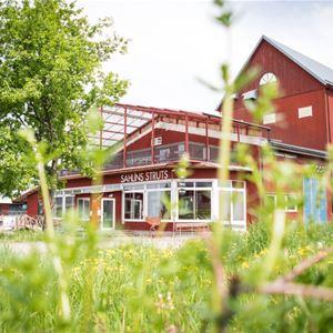 Ett stort rött hus med en balkong grönska i fokus.