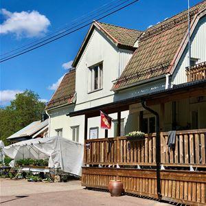 Ett vitt hus med en altan, utanför huset ett bord med blommor på.